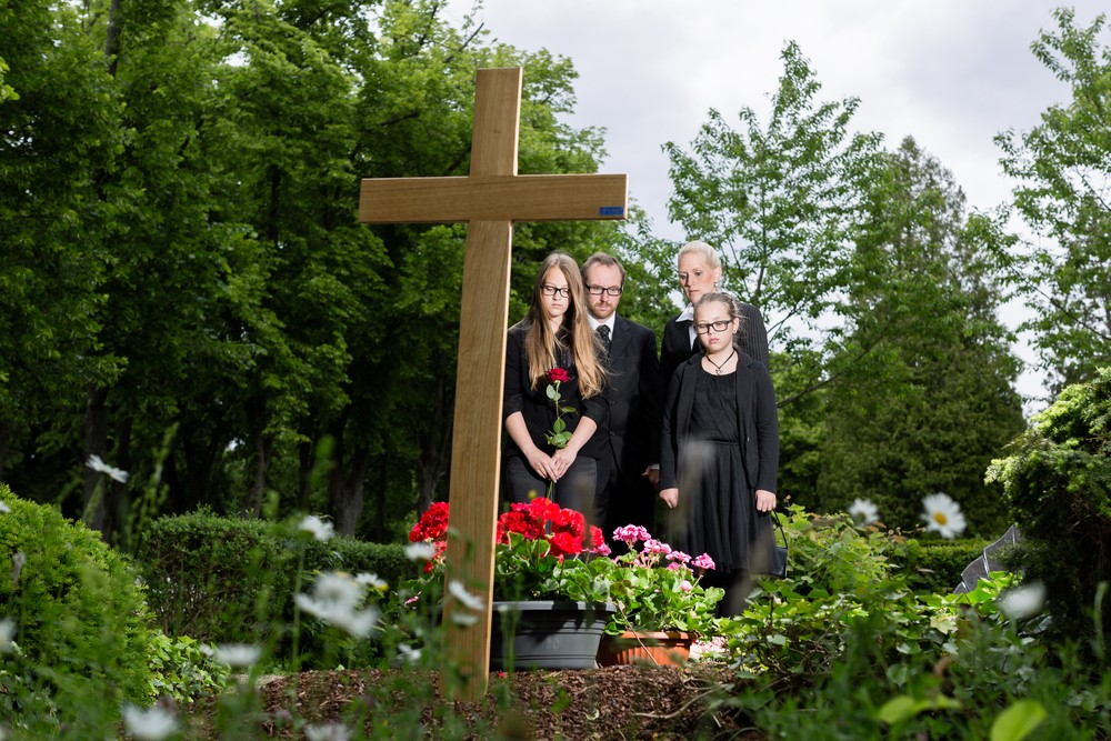 Family mourning in cemetery during burial