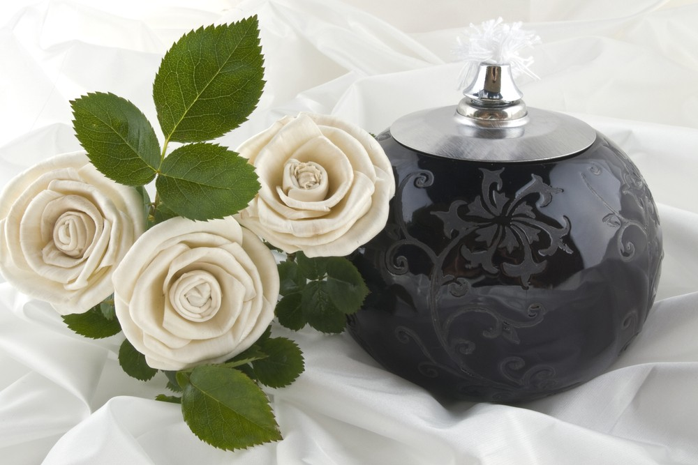 Cremation urn and white roses